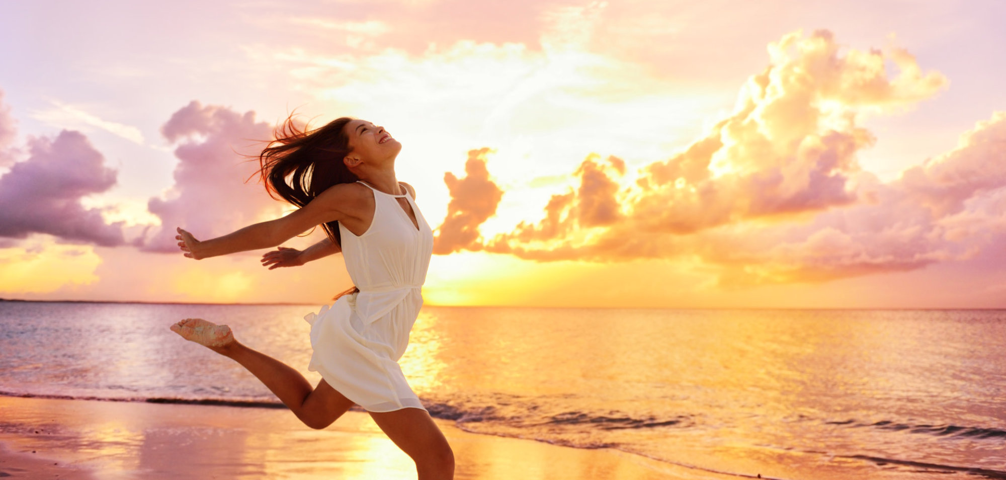 Happy carefree Asian woman feeling blissful jumping of joy on peaceful beach at sunset