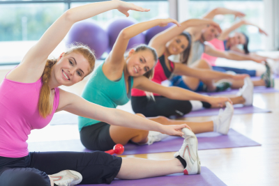 Portrait of fitness class and instructor doing stretching exercise